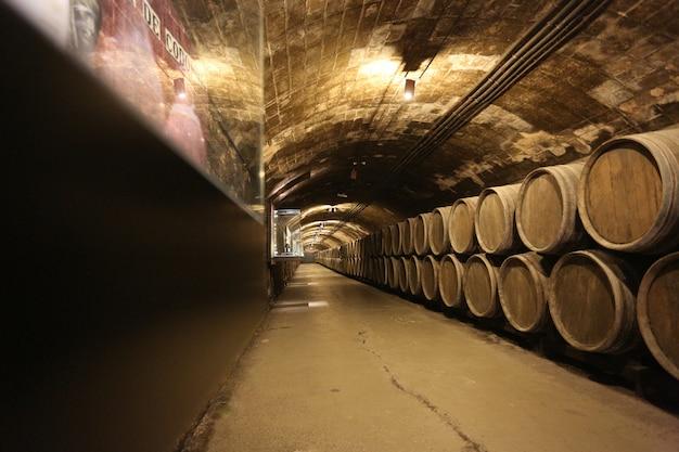 Fila de barricas viejas para el envejecimiento del vino en la bodega. Foto Premium