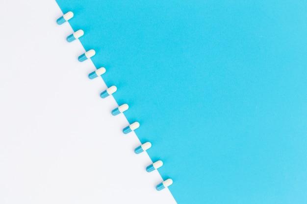 Fila de cápsulas dispuestas sobre fondo dual blanco y azul Foto gratis