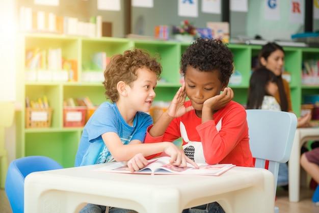 Fila de los estudiantes elementales multiétnicos que leen el libro en sala de clase. Imágenes de estilo de efecto vintage. Foto Gratis