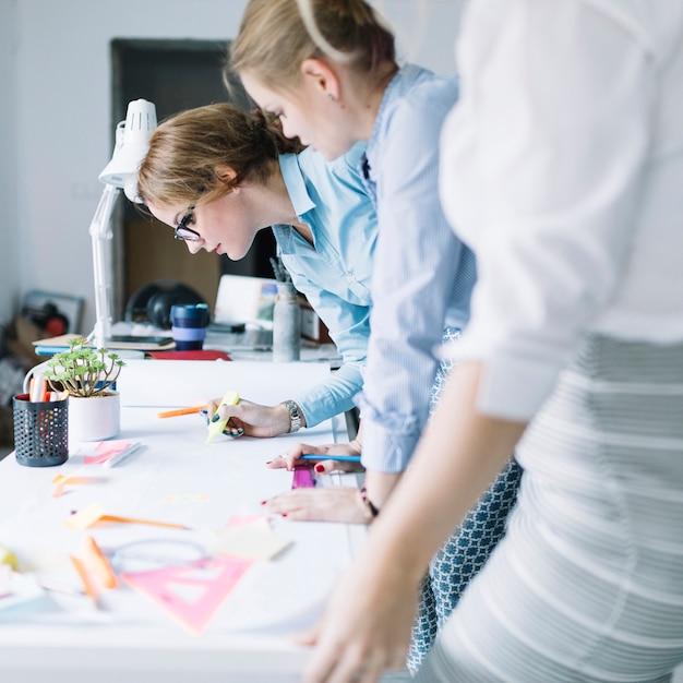 Fila de empresarias que dibujan proyecto en el libro blanco en el lugar de trabajo Foto gratis