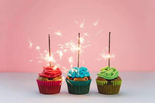 Fila de fuegos artificiales iluminados sobre los cupcakes contra fondo rosa Foto gratis