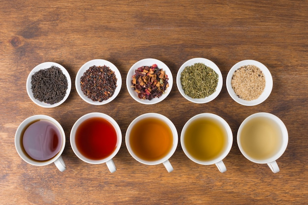 Fila de hierbas secas con aroma tazas de té blanco en mesa de madera Foto gratis