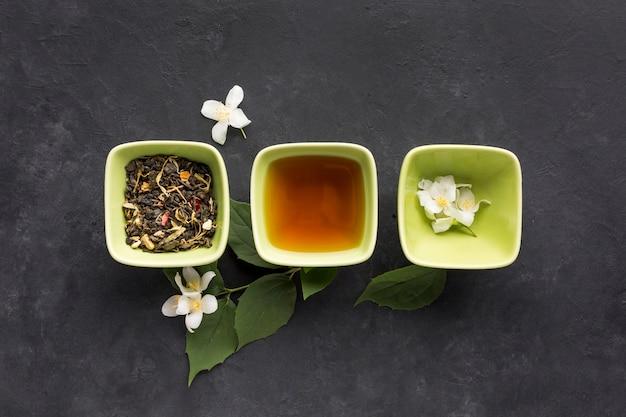 Fila del ingrediente sano del té y de la flor blanca del jazmín en superficie negra Foto gratis