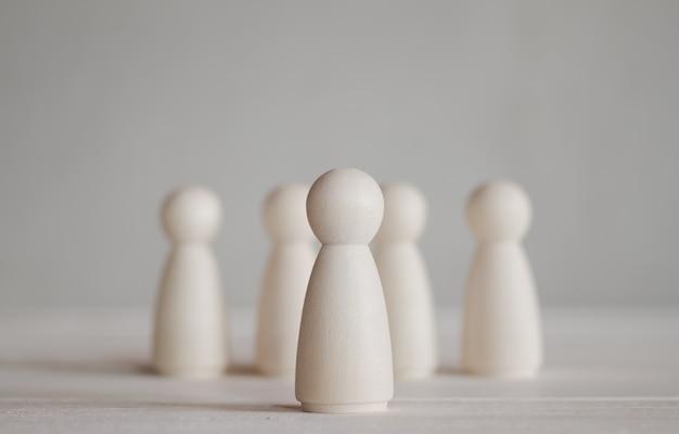 Fila de muñecas de madera de pie sobre la mesa de madera que se destacan del grupo Foto Premium