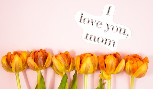 Fila de tulipanes en fondo coloful con el espacio para el mensaje. fondo del día de la madre. vista superior Foto Premium
