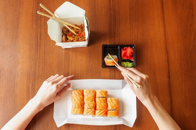 Filadelfia rollos con arroz en la mesa. salmón, queso de filadelfia, pepino, aguacate, palitos de madera en las manos. Foto Premium