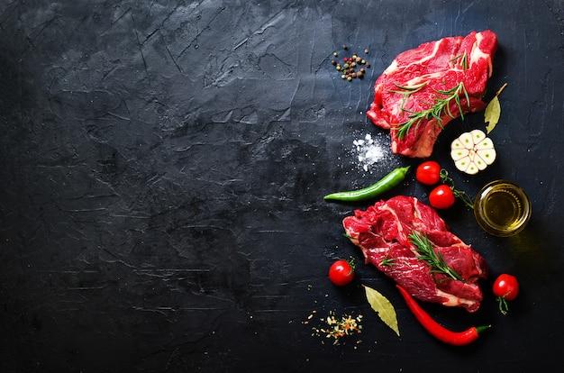 Filete de carne cruda en una tabla de cortar de piedra con hierbas Foto Premium