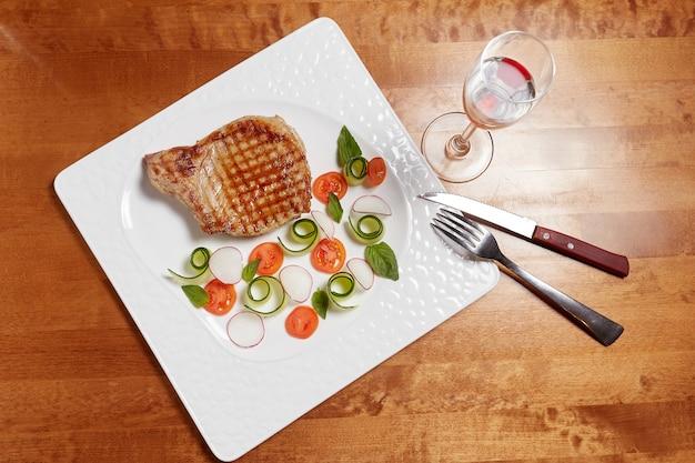 Filete de carne a la parrilla con verduras en un plato Foto Premium