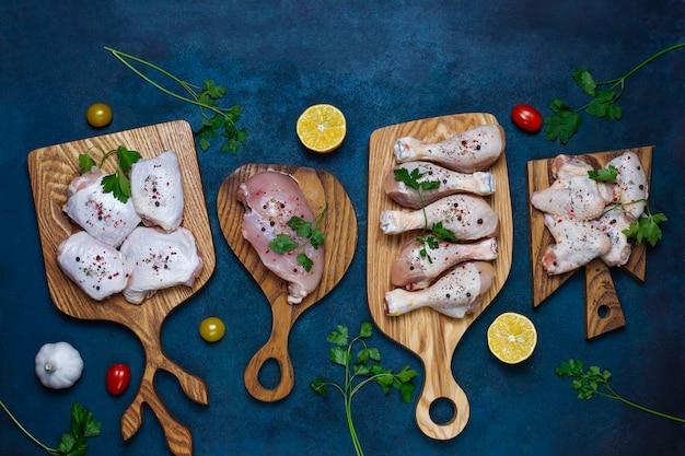 Filete de carne de pollo crudo, muslo, alas y patas con hierbas, especias, limón y ajo sobre fondo azul oscuro. vista superior Foto gratis