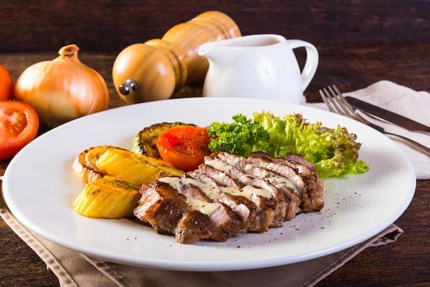 Filete del cerdo asado a la parrilla, patatas cocidas y ensalada vegetal en la tabla de madera. Foto Premium