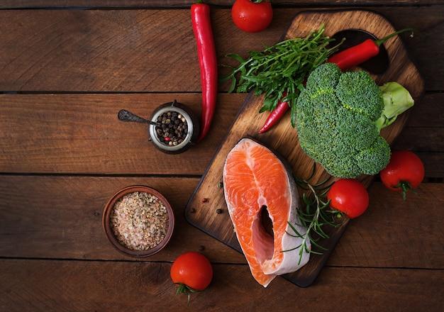 Filete crudo salmón y verduras para cocinar en la mesa de madera en un estilo rústico. vista superior Foto gratis