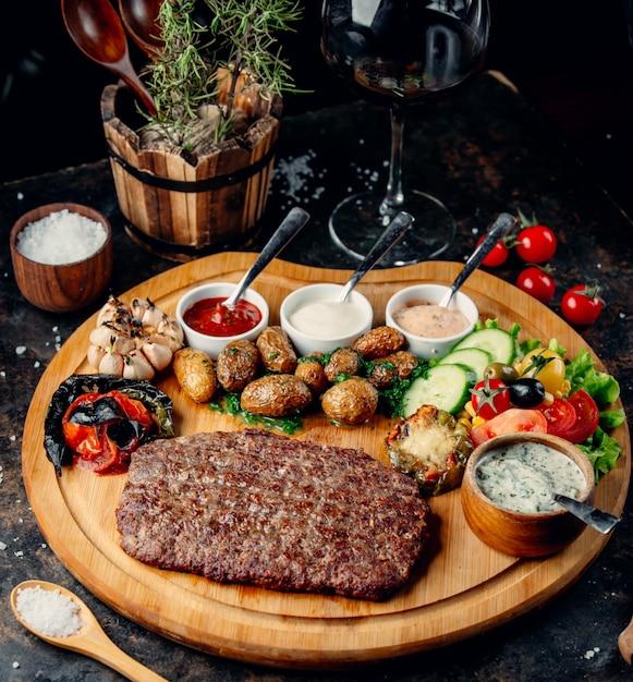 Filete con patatas y verduras sobre tabla de madera Foto gratis