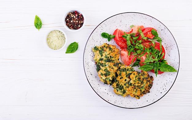 Filete de pollo al horno con espinacas y una guarnición de ensalada de tomates. cocina europea. comida dietética vista superior Foto gratis