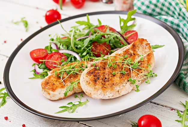 Filete de pollo a la parrilla y ensalada de vegetales frescos de tomate, cebolla roja y rúcula. ensalada de carne de pollo. comida sana. Foto gratis