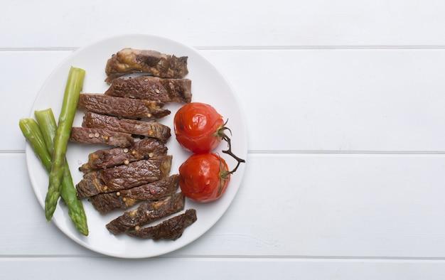 Filete de res a la parrilla en un plato blanco y fondo blanco, plano y espacio de copia Foto Premium