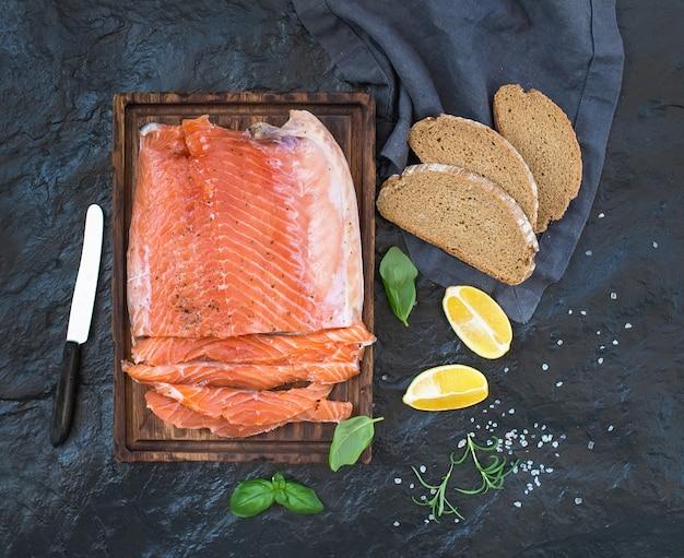 Filete de salmón ahumado con limón, hierbas frescas y criado en una tabla de madera sobre fondo de piedra oscura Foto Premium