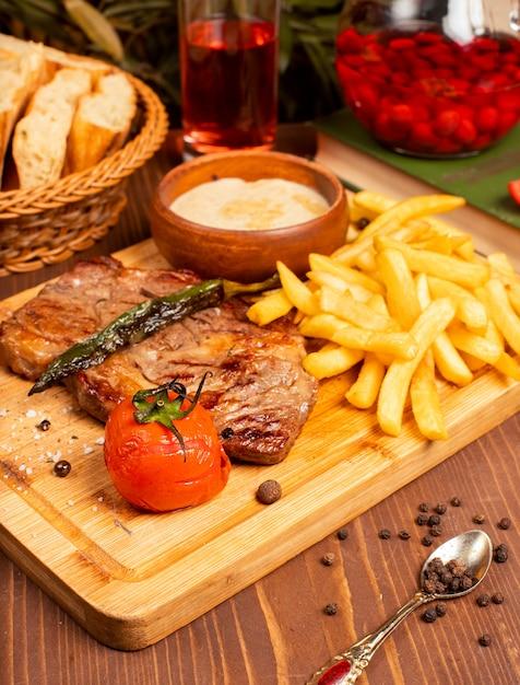 Filete de ternera con papas fritas, salsa de mayonesa con crema agria y hierbas en un plato de madera Foto gratis