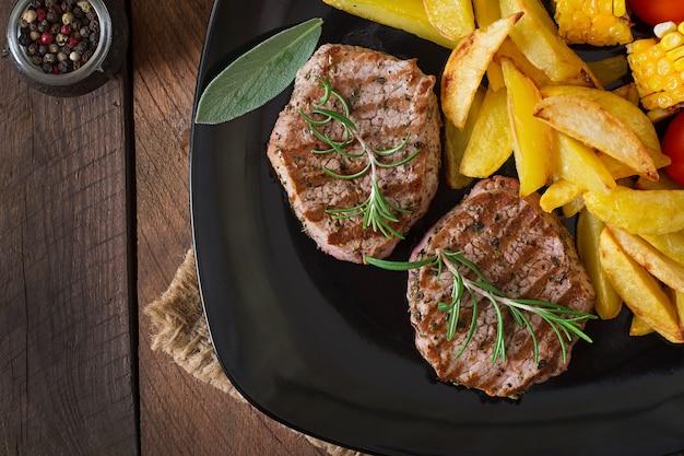 Filete de ternera tierno y jugoso medio raro con papas fritas Foto Premium