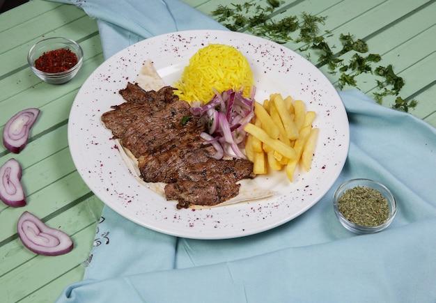 Filetes de carne con papas fritas y guarnición de arroz Foto gratis