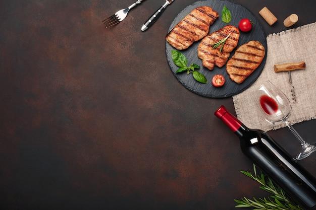 Filetes de cerdo a la parrilla en piedra con botella de vino, copa de vino, cuchillo y tenedor sobre fondo oxidado Foto Premium