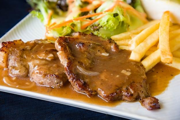 Filetes a la parrilla, papas fritas hervidas y ensalada de verduras Foto Premium