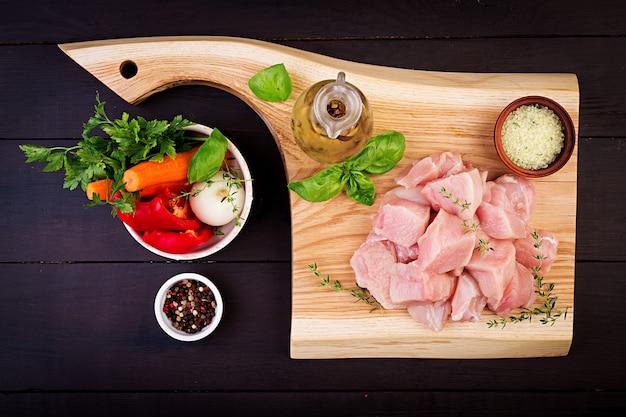 Filetes de pechuga de pollo cruda en tabla de cortar de madera con hierbas y especias. vista superior Foto gratis