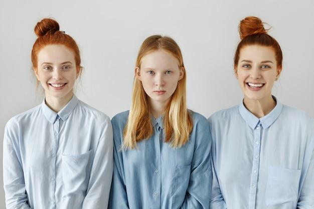 Filmación en interiores de tres mujeres caucásicas en camisetas similares posando en la pared del estudio en blanco Foto gratis