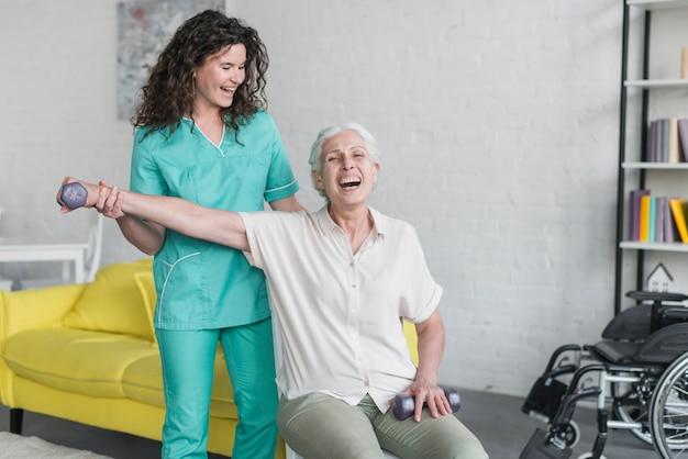 Fisioterapeuta ayuda a mujer mayor para hacer ejercicio con pesas Foto gratis