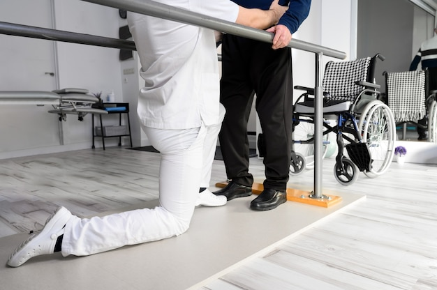 Fisioterapeuta ayudando al hombre mayor caucásico discapacitado a caminar con barras paralelas en el centro de rehabilitación. Foto Premium