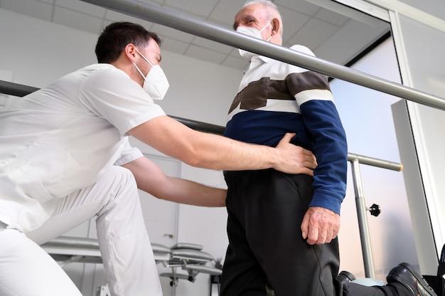Fisioterapeuta ayudando al paciente mayor a caminar entre barras paralelas. Foto Premium