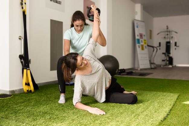Fisioterapeuta ayudar a la mujer caucásica joven con ejercicio con mancuernas Foto gratis