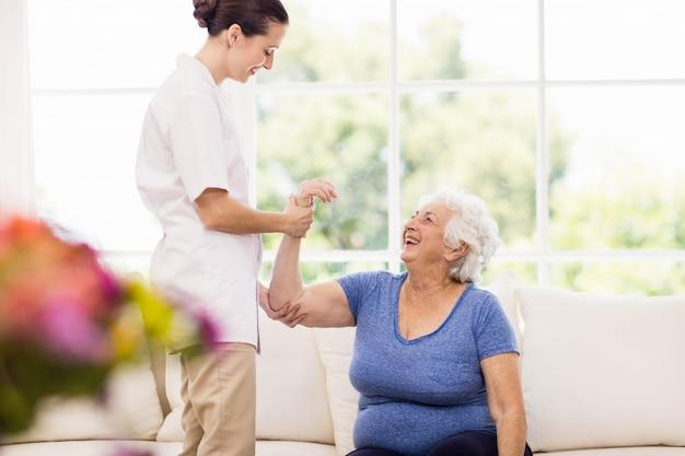 Fisioterapeuta cuidando paciente anciano enfermo en casa Foto Premium