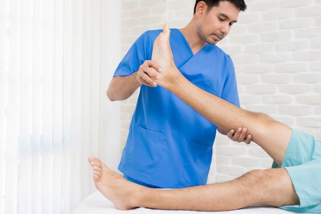 Fisioterapeuta entrenando ejercicio de rehabilitación a paciente masculino en el hospital Foto Premium