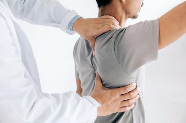 Fisioterapeuta haciendo tratamiento curativo en la espalda del hombre. paciente con dolor de espalda, tratamiento Foto Premium