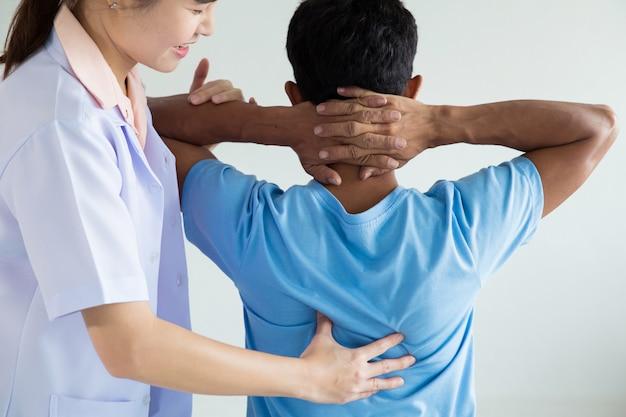 Fisioterapeuta haciendo tratamiento curativo en la espalda del hombre. Foto Premium