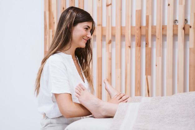 Fisioterapeuta mujer dando un masaje de pies a paciente en clínica Foto Premium