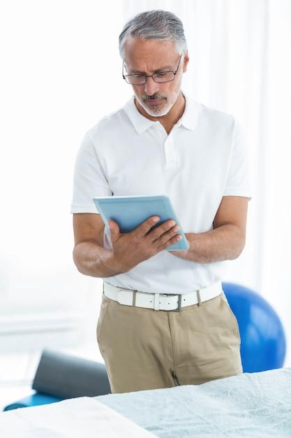 Fisioterapeuta con tableta digital en casa Foto Premium