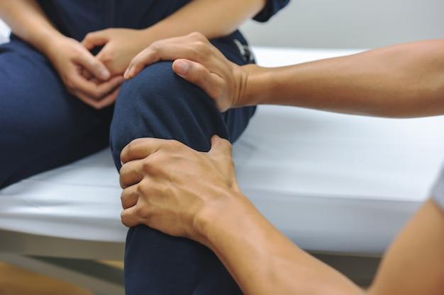Los fisioterapeutas están revisando las lesiones de rodilla para el paciente. concepto médico y sanitario Foto Premium