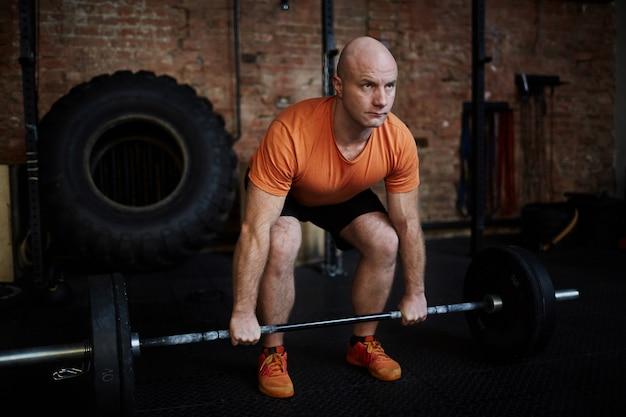 Fit man lifting barbell Foto gratis