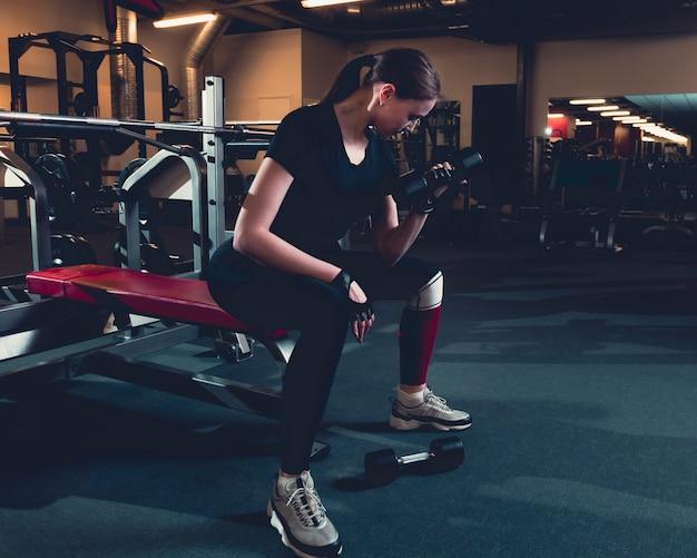 Fit mujer haciendo ejercicios de bíceps con pesas en el gimnasio Foto gratis