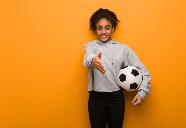 Fitness mujer joven negro llegar a saludar a alguien. sosteniendo un balón de fútbol. Foto Premium