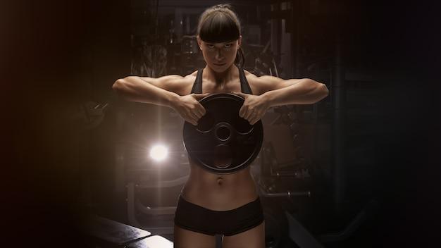 Fitness mujer muscular mano fuerte bombeo de músculos con placa Foto Premium