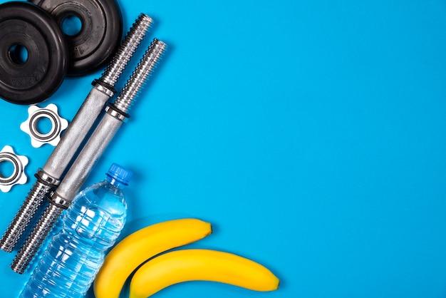 Fitness o culturismo. equipamiento deportivo, plátano, botella de agua, barra, mancuerna, vista superior Foto Premium