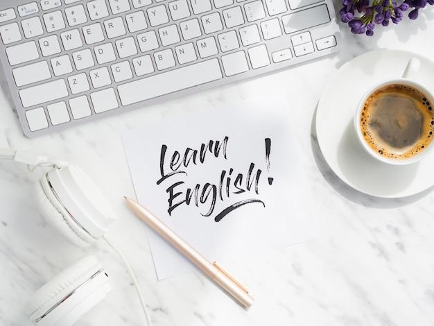 Flat lay aprender mensaje en inglés en nota adhesiva Foto gratis