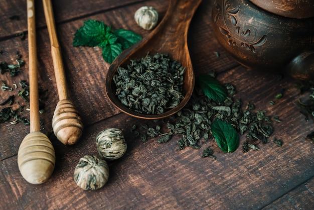 Flat lay variedad de hierbas de té y palitos de miel Foto gratis