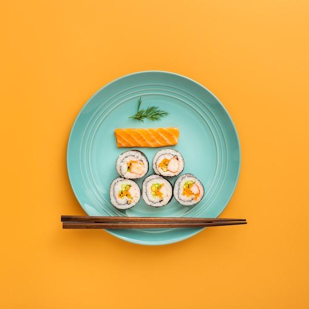Flat pone nigiri y maki sushi con palillos Foto gratis
