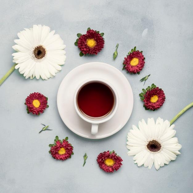 Flay pone una taza de té de frutas y un arreglo de margaritas Foto gratis