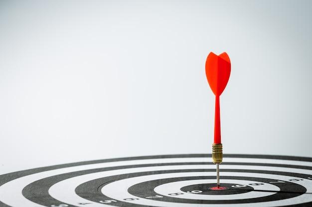 Flecha de dardo golpeando en el centro del blanco del tablero de dardos Foto Premium