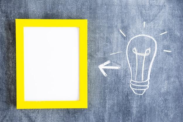Flecha entre marco blanco con borde amarillo y bombilla de luz en la pizarra Foto gratis