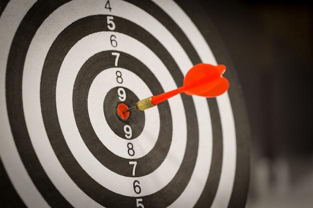 Flecha roja del dardo que golpea en el centro objetivo. Foto Premium
